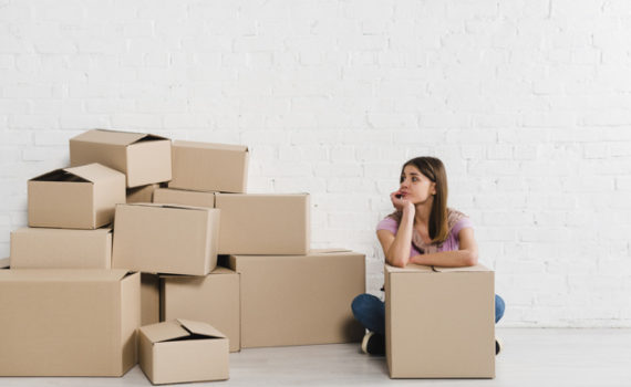 depressed-young-woman-looking-cardboard-boxes_23-2148095478